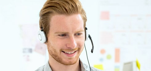 Man smiling while talking on a headset